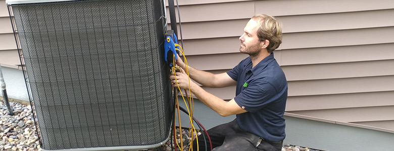 a man servicing and air conditioning unit.